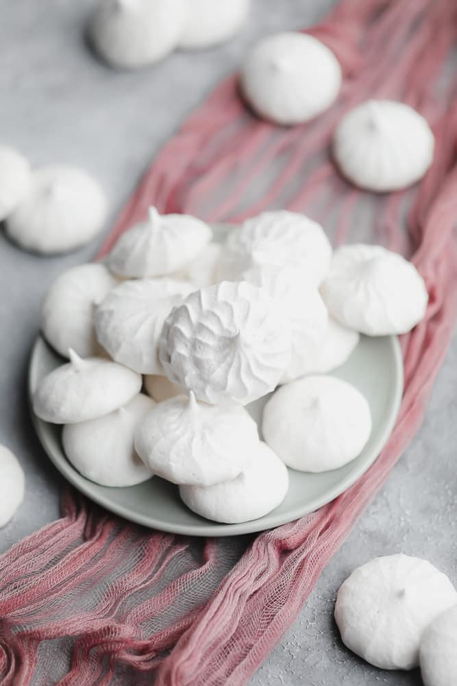White vegan meringues cookies on a small grey plate