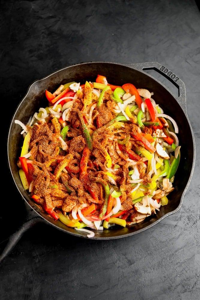 raw sliced veggies with seasonings on top in a black skillet