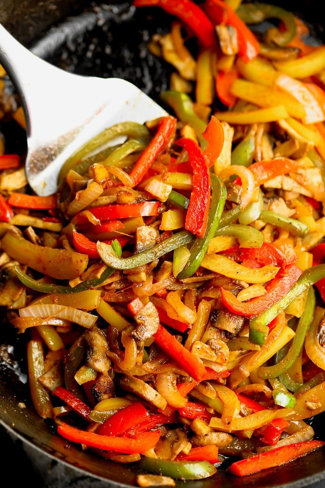 close up on a spatula mixing sliced bell peppers, onions, and mushrooms in a skillet
