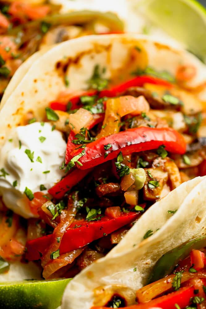 close up on a tortilla stuffed with cooked red bell peppers and onions