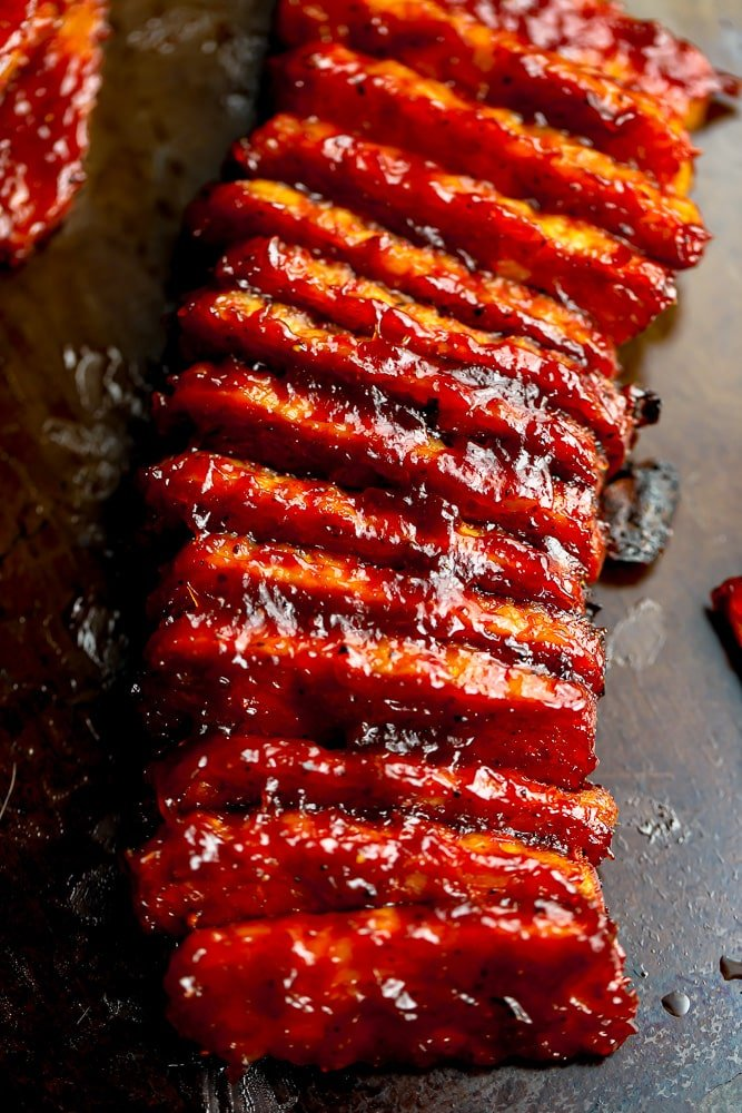 many tempeh pieces with bbq sauce on a pan