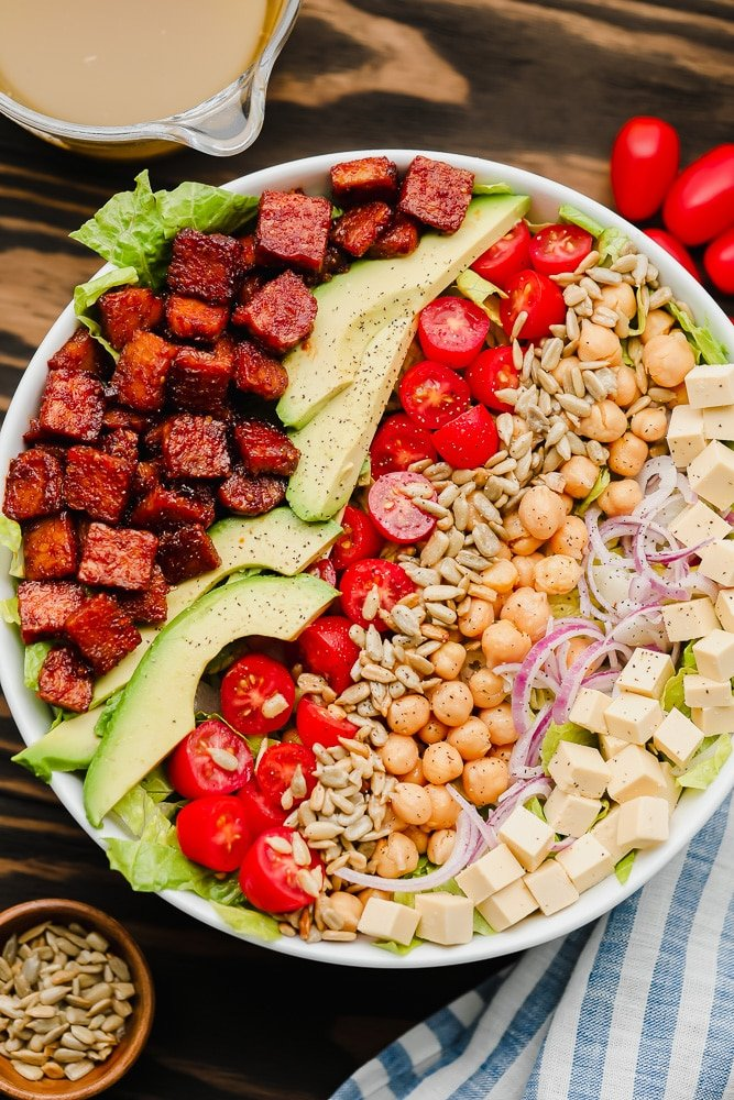 lines of vegan bacon, avocado, tomatoes, seeds, and beans on top of lettuce in a white bowl