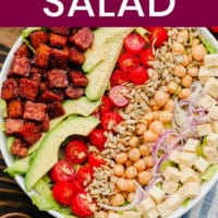 pinterest image of lines of vegan bacon, avocado, tomatoes, seeds, and beans on top of lettuce in a white bowl