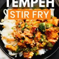 pinterest image of tempeh and broccoli stir fry on top of white noodles in a black bowl