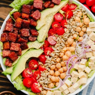 close up of lines of vegan bacon, avocado, tomatoes, seeds, and beans on top of lettuce in a white bowl