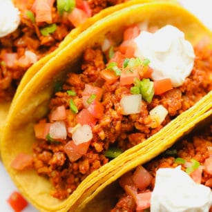 close up on a corn tortilla tempeh taco topped with tomatoes and sour cream