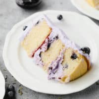 piece of cake on a plate with blueberries and purple frosting