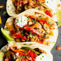 3 tortillas in a row stuffed with sauteed bell peppers, onions, and mushrooms