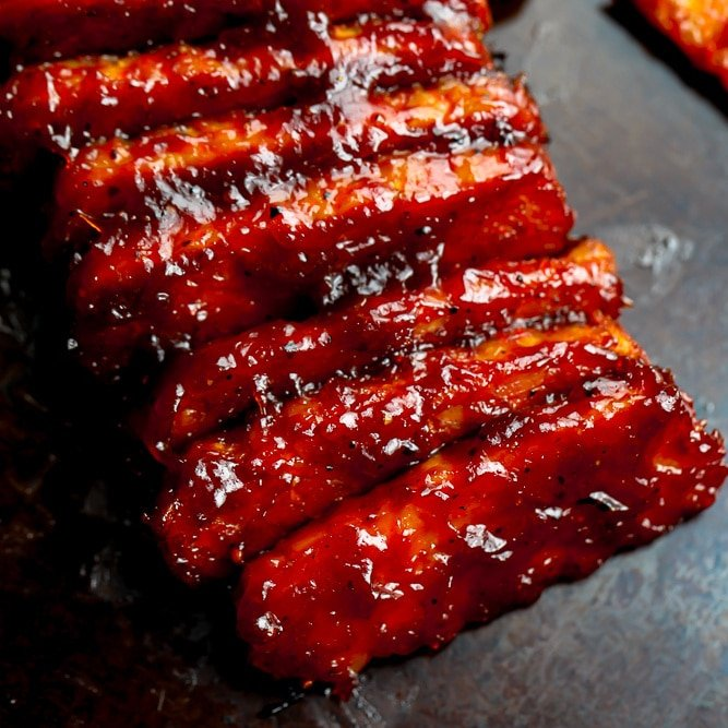 square image of lined up tempeh ribs with bbq sauce