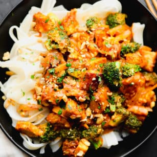 close up on a tempeh and broccoli stir fry on top of white noodles in a black bowl