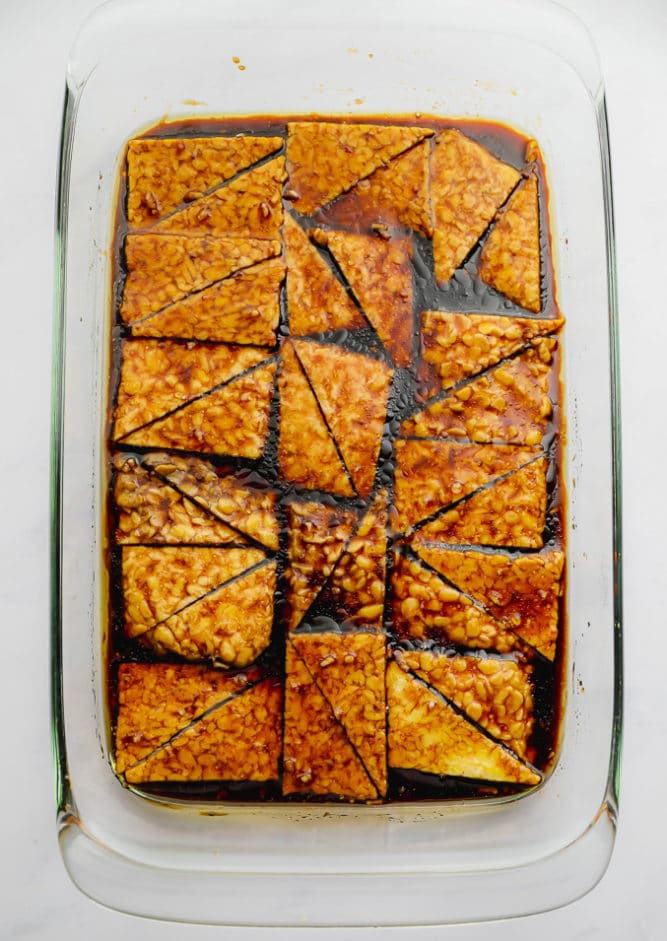 tempeh marinating in a large glass dish