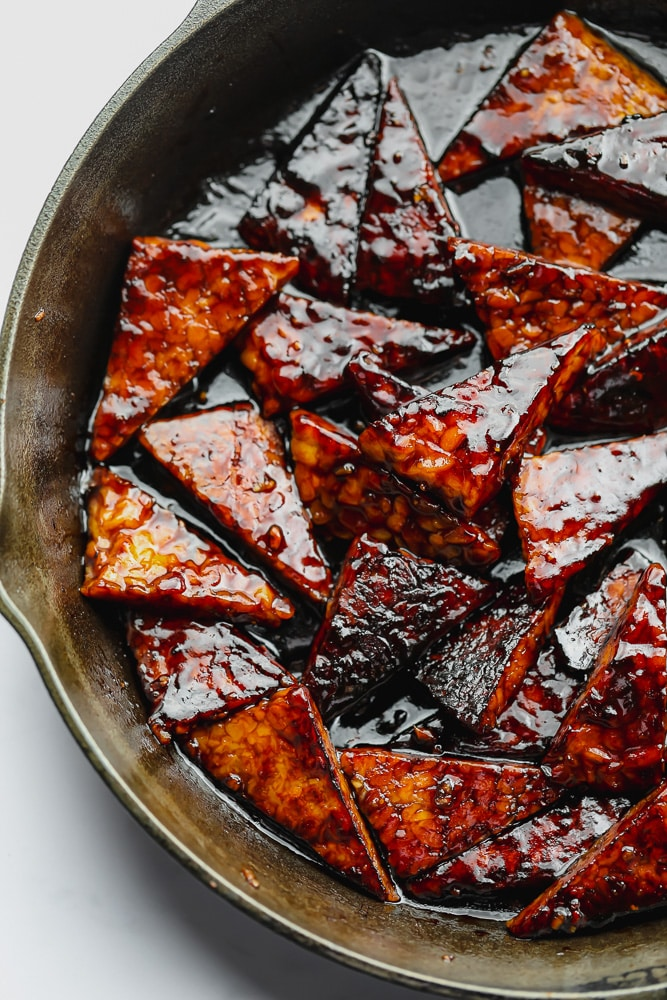 cast iron pan filled with triangles of tempeh with sticky sauce