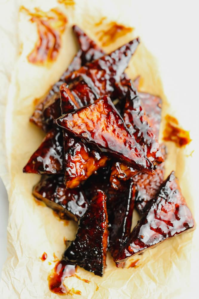 meat looking triangles on parchment paper with white background and reddish brown sauce