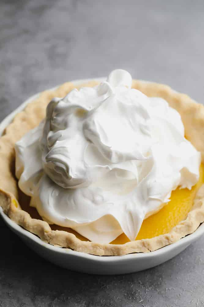 a big mound of whipped white meringue on top of a lemon pie
