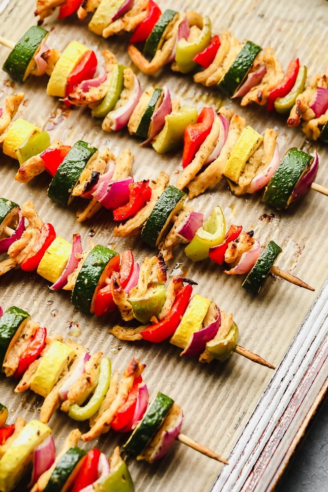 cooked vegetable kebabs on a parchment lined baking sheet