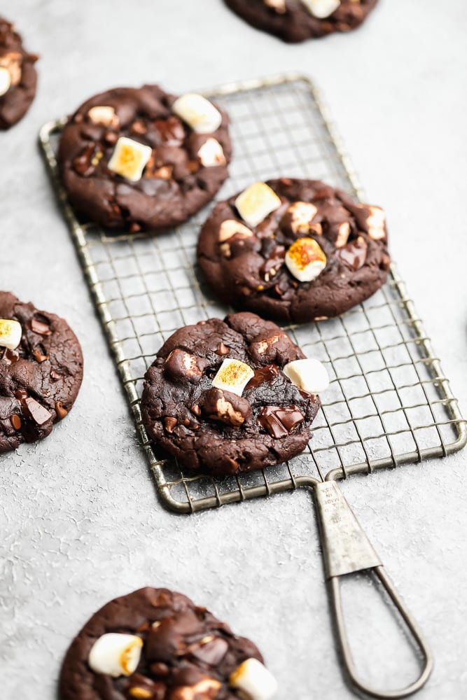 3 baked chocolate marshmallow cookies on a wire cooling rack