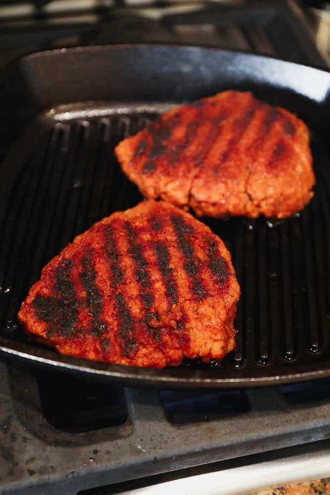grilling 2 orange seitan patties in a black grill pan