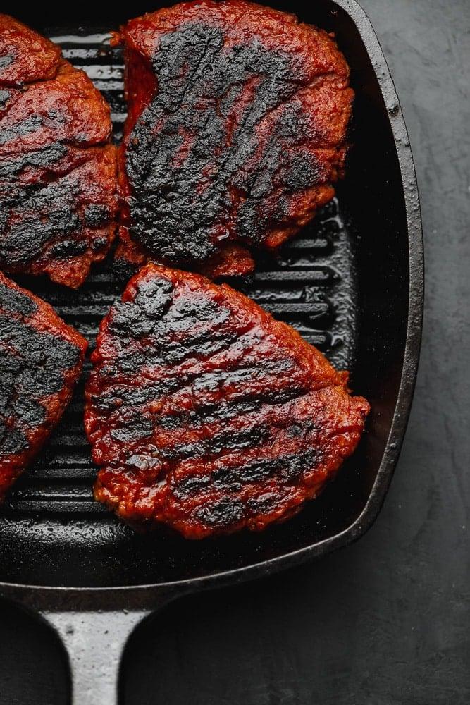 4 charred vegan steak patties in a black grill pan