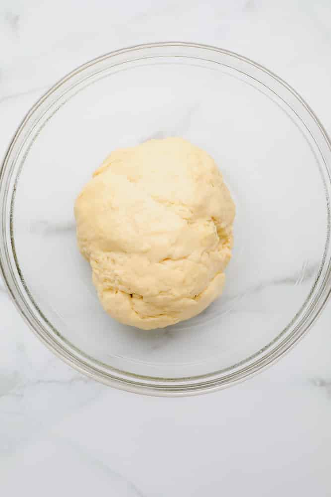 small ball of raw bread dough in a glass bowl