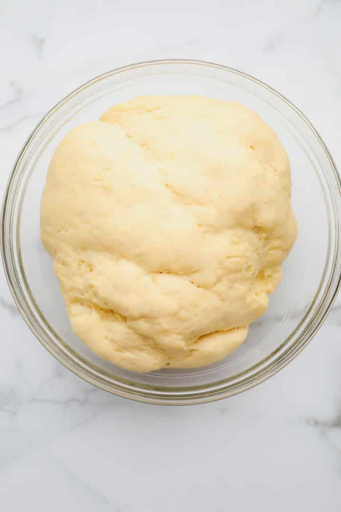 large ball of raw bread dough in a glass bowl