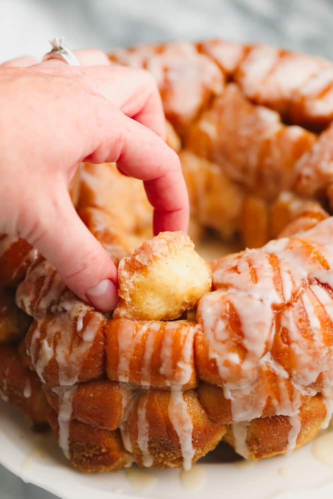 womans hand taking a ball of dough from loaf of baked golden brown monkey bread