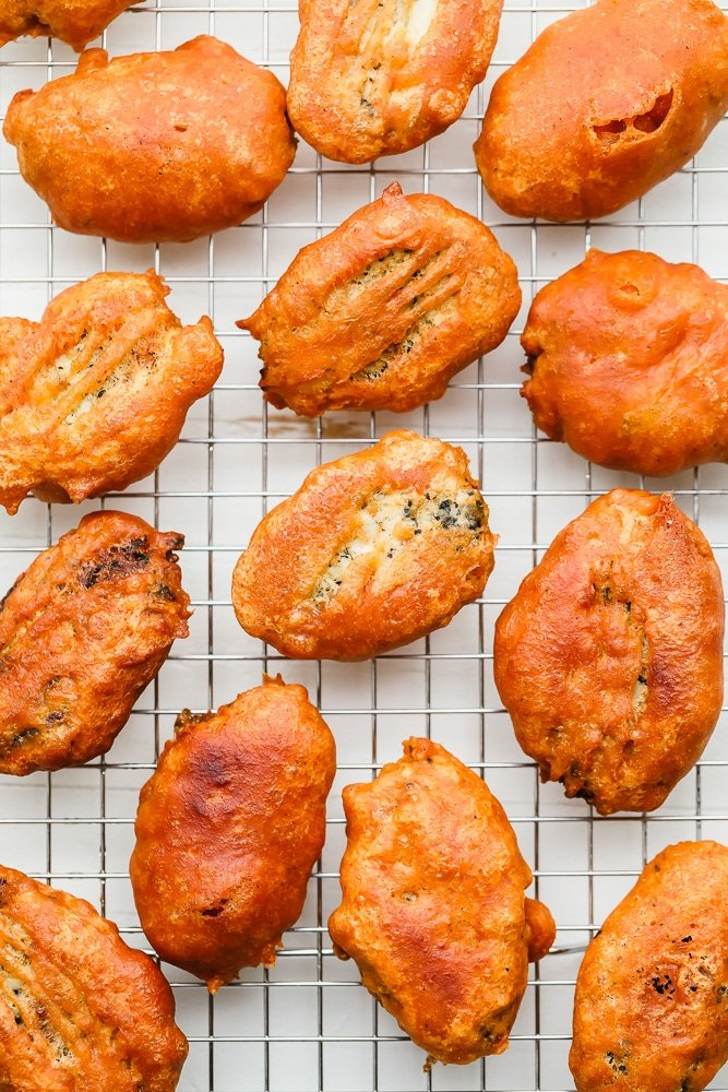 pieces of golden brown fried vegan fish on a wire rack