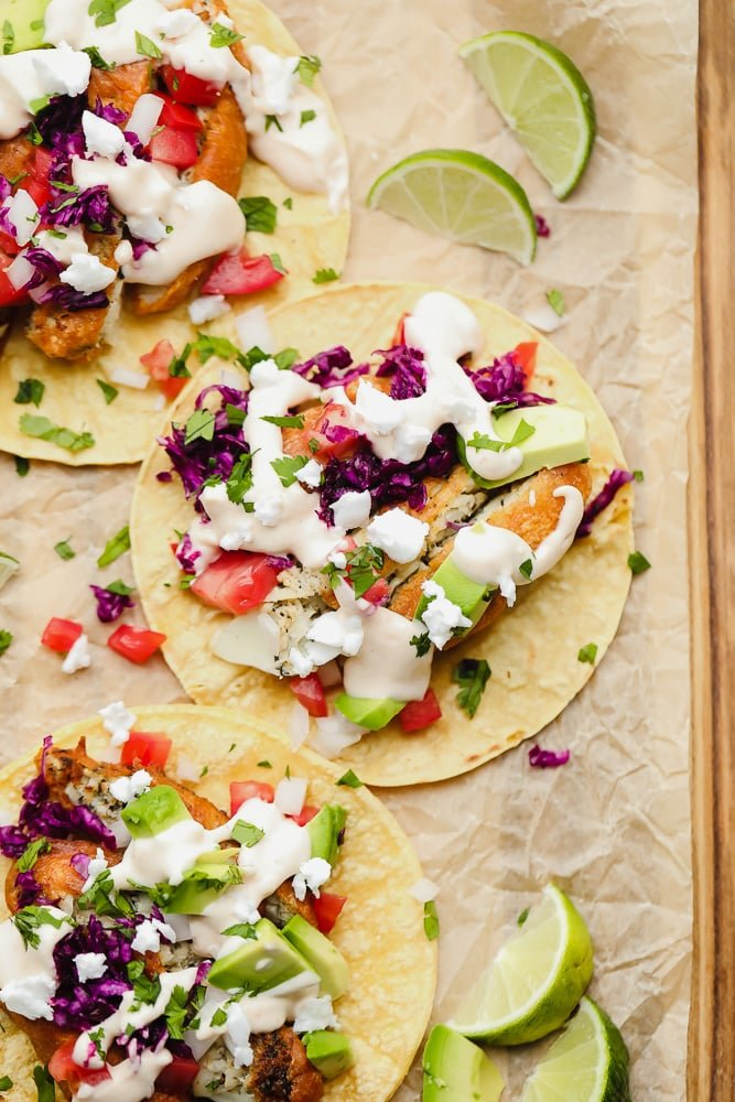 corn tortillas topped with vegan fish, purple cabbage, and a white sauce on parchment paper