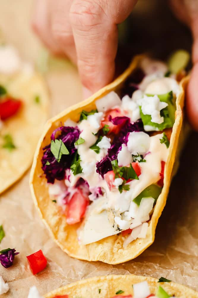 a hand picking up a corn tortilla filled with white sauce, tomatoes, and purple cabbage