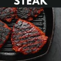 pinterest image of 4 charred vegan steaks in a black grill pan