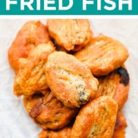 pinterest image of a pile of golden brown vegan fried fish on a piece of white parchment paper