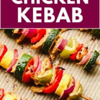 pinterest image of cooked vegetable kebabs on a baking sheet
