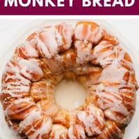 pinterest image of baked golden brown monkey bread on a white plate, covered in white icing