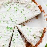 cut slices of key lime pie in a white pie plate