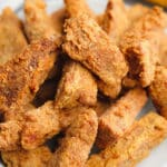 close up on a large plate filled with golden brown fried vegan chicken pieces