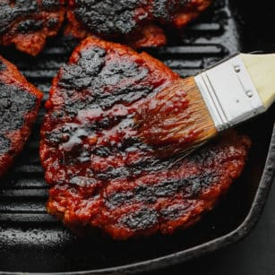 brushing red sauce on a charred vegan steak in a grill pan