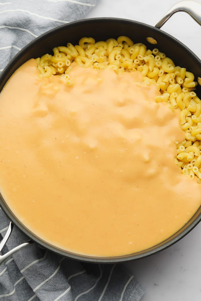 orange cheese sauce covering cooked macaroni in a large black skiller