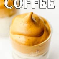 pinterest image of a glass with milk topped with whipped coffee