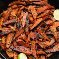 square image of carne asada made vegan in a black pan
