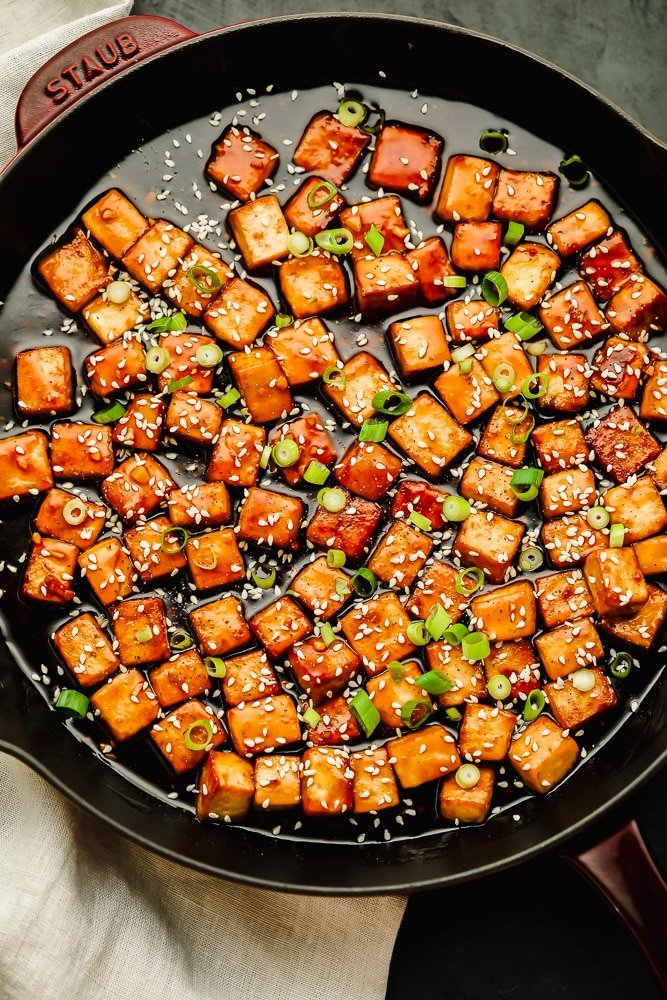 baked tofu cubes covered in a brown sauce in a large black skillet