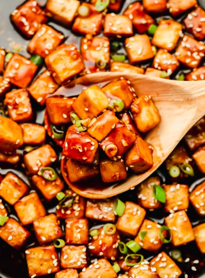 wooden spoon taking a scoop of sauce-covered tofu cubes out of a skillet