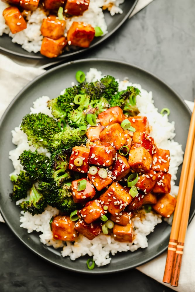 saucy brown tofu over white rice and cooked broccoli on a grey plate with chopsticks