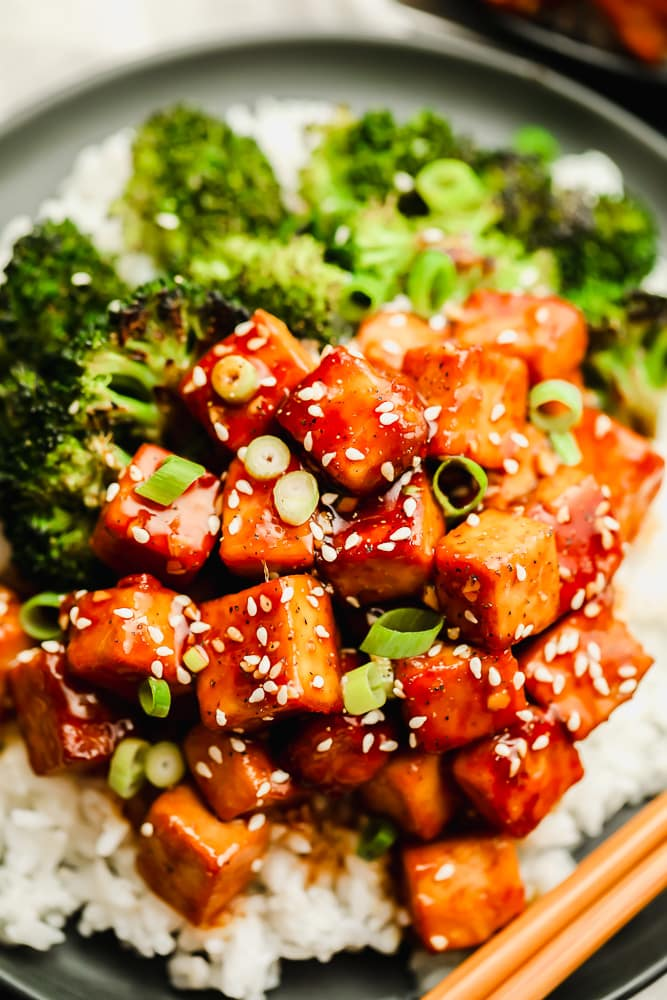 close up on brown saucy tofu on a plate with white rice and broccoli