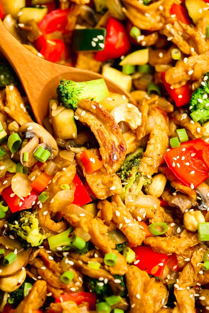 close up on a wooden spoon scooping vegetables and soy curls from a stir fry