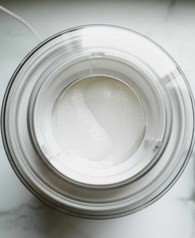 overhead view of an ice cream maker with a white creamy mixture inside