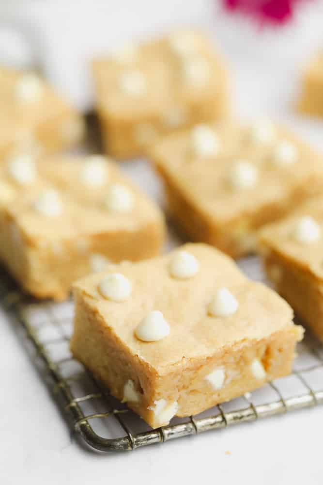baked blondies cut into squares sitting on a wire rack