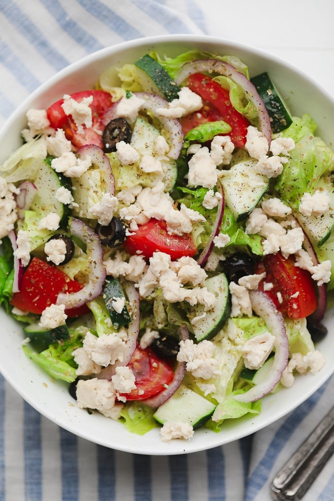 a Greek salad in a white bowl topped with crumbled white vegan feta cheese.
