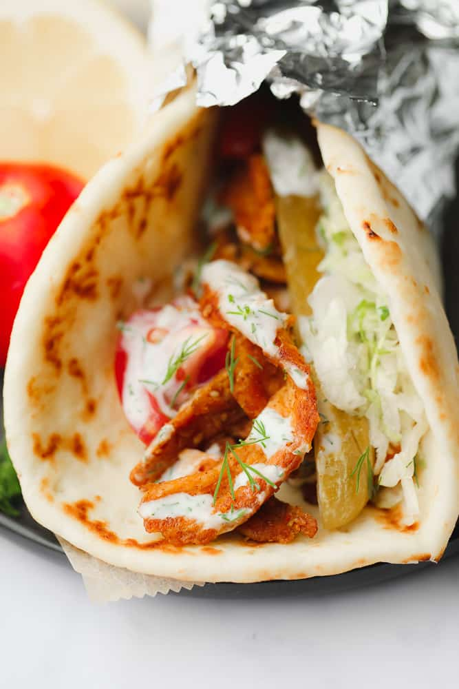 close up on a vegetable shawarma wrapped in tin foil.