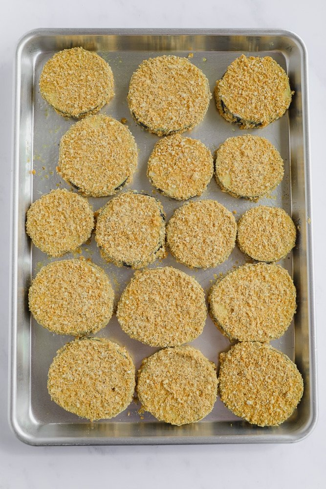 eggplant slices coated in crumbs lined on a baking tray