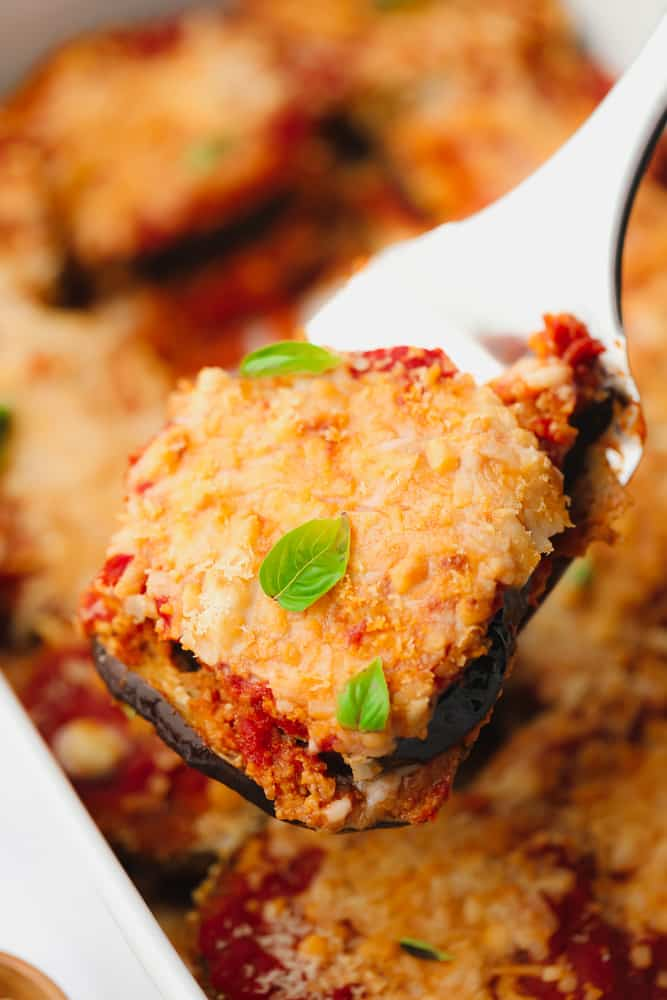 close up on a scoop of eggplant parmesan with melted cheese and herbs on top.