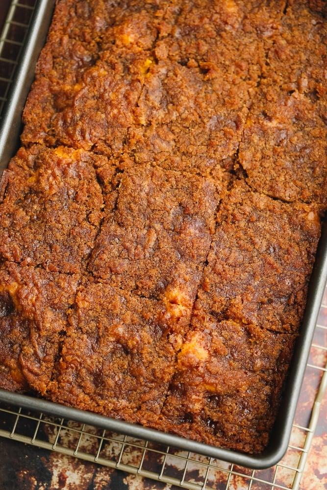 dark brown baked cake cut into squares in a metal baking tin.